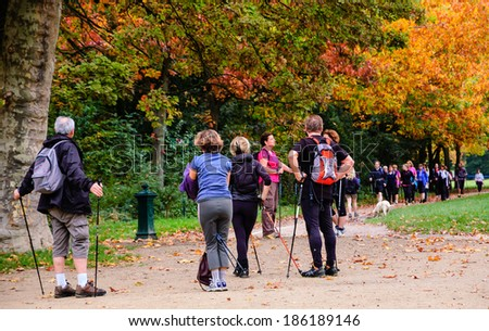 PARIS, FRANCE - OCTOBER 26, 2013: Unidentified people walk with sticks (Nordic walking) in Vincennes forest of Paris. Medical studies show that walking can reduce the risk of stroke in elderly people. - stock photo