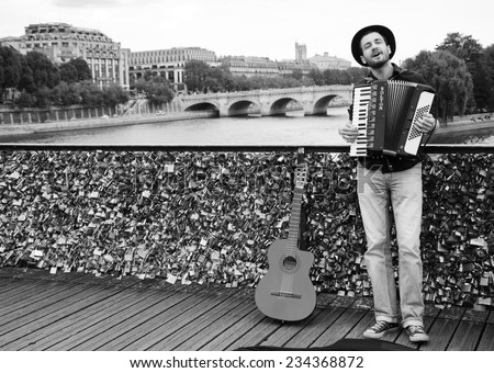 PARIS, FRANCE - OCTOBER 4, 2014: Unidentified young musician plays accordion on the Love Locks bridge . Dozens buskers perform on the streets and in the metro of Paris. - stock photo