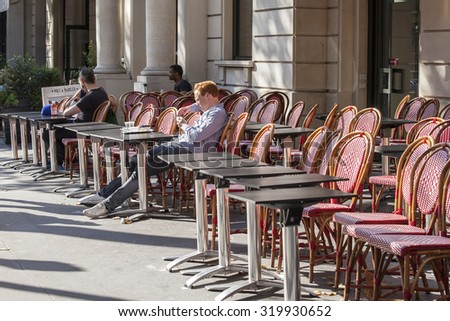 PARIS, FRANCE, on AUGUST 26, 2015. Picturesque summer cafe on the city street, red wattled chairs