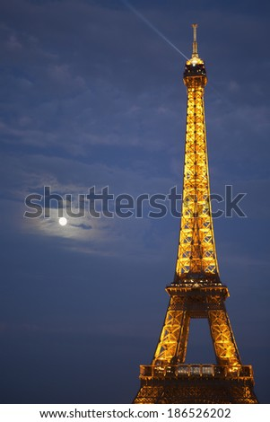 PARIS, FRANCE - SEPTEMBER 10, 2011: Artificially illuminated Eiffel tower with the rising moon in the background. Originally was built for radio station and now is one of the most visited landmarks.  - stock photo