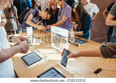 PARIS, FRANCE - SEPTEMBER 20, 2014: Customers admiring the new Apple iPhone 6 and iPhone 6 Plus at the Apple Inc. store in Paris, France - stock photo