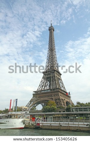 PARIS, FRANCE-SEPTEMBER, 10: Eiffel Tower and Bateau Mouche on September 10, 2012 in Paris. The Eiffel Tower is the most visited monument of France with about 6 million visitors every year. - stock photo