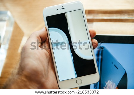 PARIS, FRANCE - SEPTEMBER 20, 2014: Hand holding a iPhone 6 Plus displaying the welcome note during the sales launch of the latest Apple Inc. smartphones at the Apple store in Paris, France - stock photo