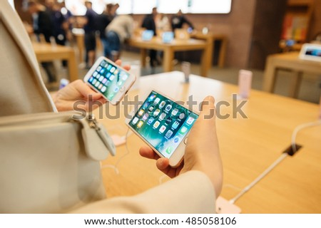PARIS, FRANCE - SEPTEMBER 16, 2016: New Apple iPhone 7 Plus being tested by woman after purchase - comparing the iPhone 7 vs iPhone 7 plus