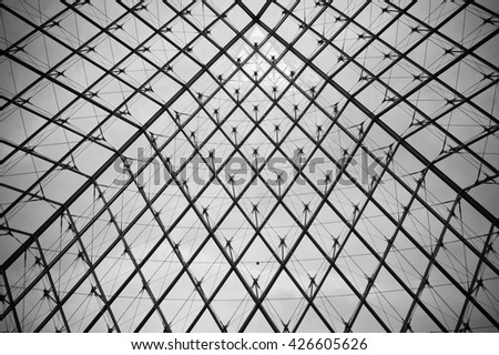 PARIS, FRANCE - 08.16.2004. - The Pyramid abstract metal and glass view inside the Louvre museum, black and white image - stock photo