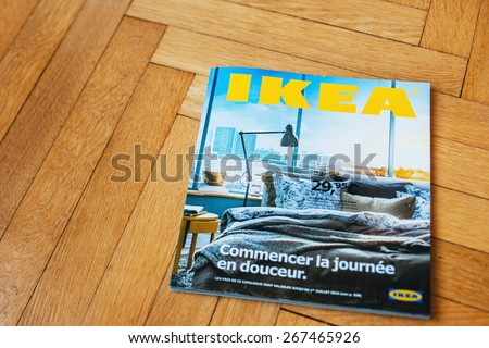 PARIS, FRNACE - AUGUST 28, 2014: IKEA Catalog lying on wooden parquet floor. Ikea is the world's largest furniture retailer, founded in Sweden. - stock photo