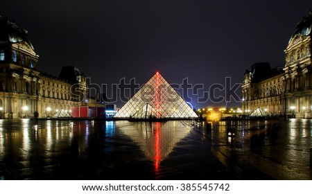 PARIS - JAN 1. Louvre museum at night on January, 1, 2016. The Louvre is the biggest museum in Paris with nearly 35,000 objects from prehistory to the 19th century are exhibited there. - stock photo