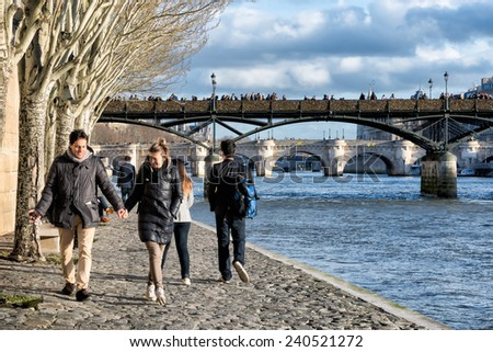 PARIS-JAN 2, 2014: People walking along the river Seine, a favorite activity for visitors and Parisians. Above is a view of the famous Pont des Arts bridge covered with love locks. - stock photo