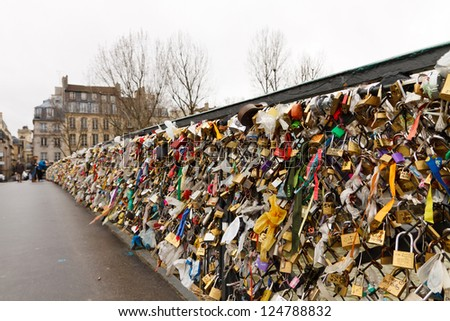 PARIS - JANUARY 1: Love padlocks at Pont de l'Archeveche on January 1, 2012, in Paris. The thousands of locks of loving couples symbolize love forever. - stock photo