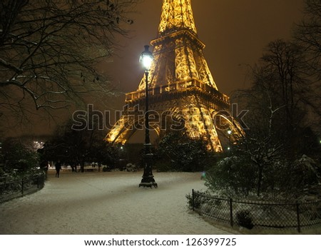 PARIS -JANUARY 20: Romantic snowy park near the Eiffel Tower, January 20, 2013. Snowing is very rare event  in Paris, and Eiffel Tower is particularly beautiful when seeing from snowy parisian parks.