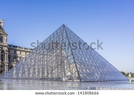 PARIS - JULY 24: Pyramid near Louvre building on July 24, 2012 in Louvre Museum, Paris, France. With 8.8 million annual visitors, Louvre is consistently the most visited museum worldwide.