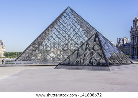 PARIS - JULY 24: Pyramid near Louvre building on July 24, 2012 in Louvre Museum, Paris, France. With 8.8 million annual visitors, Louvre is consistently the most visited museum worldwide. - stock photo