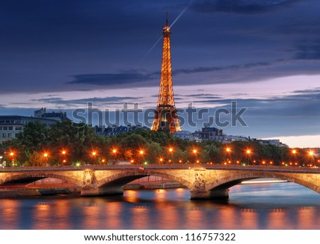 PARIS - JULY 30: The illuminated Eiffel Tower and bridge Pont des Invalides on July 30, 2012 in Paris, France. The bridge is constructed for the upcoming 1855 World Fair in Paris. - stock photo