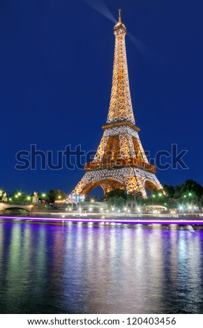 PARIS - JULY 30: The illuminated Eiffel Tower and river Seine on July 30, 2012 in Paris, France. The Eiffel Tower is most famous sights of Paris. - stock photo