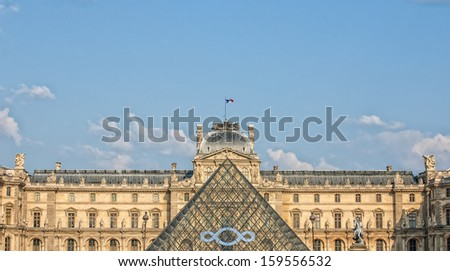PARIS - JULY 25: The Louvre museum and the Pyramid on July 25, 2013 in Paris. Louvre is the biggest Museum in Paris displaying over 60,000 square meters of exhibition space. - stock photo