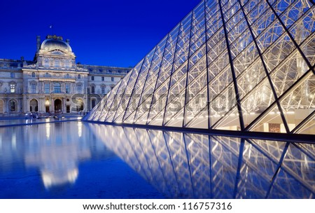 PARIS - JULY 30: The Pyramid near to the Louvre Museum on July 30, 2012 in Paris, France. Louvre Museum is one of the world's largest museums, every year museum visits more than 8 million visitors. - stock photo