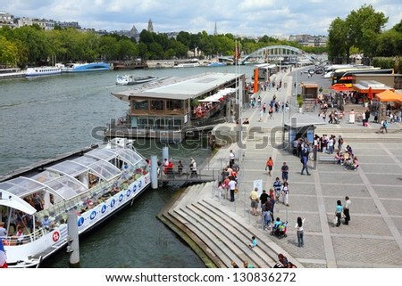 PARIS - JULY 25: Tourists walk along river Seine on July 25, 2011 in Paris, France. Paris is the most visited city in the world with 15.6 million international arrivals in 2011. - stock photo