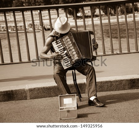 PARIS - JULY 6: Unidentified senior musician play accordion on the bridge on July 6, 2013 in Paris, France. Dozens buskers perform on the streets and in the metro of Paris. - stock photo