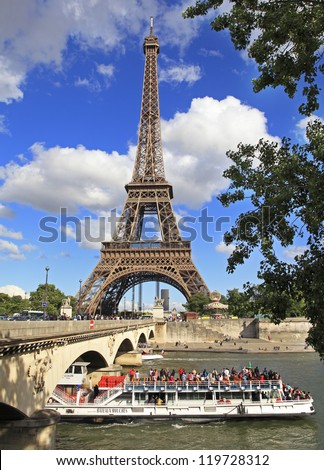 PARIS - JUNE 7: Eiffel Tower and Bateau Mouche on June 7, 2012 in Paris. The Eiffel Tower is the most visited monument of France with about 6 million visitors every year. - stock photo