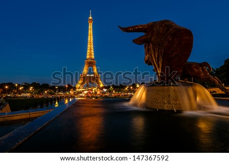PARIS - JUNE 29: Eiffel Tower light show at dawn on June 29, 2013 in Paris, France. Eiffel Tower is the highest and most visited monument in France and use 20,000 light bulbs in the night show. - stock photo