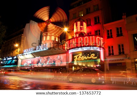PARIS - JUNE 5 - Moulin Rouge by night photographed with a long exposure with traffic blurring by June 5, 2013, Paris, France. Moulin Rouge (French for Red Mill) is a cabaret in Paris, France. - stock photo