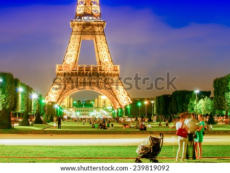 PARIS - JUNE 16, 2014: The Eiffel Tower and its lights with tourists on Champs de Mars. The tower is the most visited monument in France. - stock photo