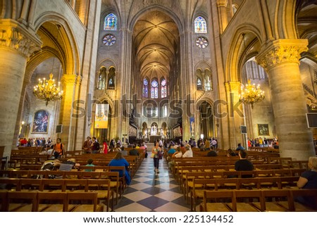 PARIS - JUNE 21: Unidentified tourists visiting the Notre Dame de Paris on June 21, 2014 in Paris. The cathedral of Notre Dame is one of the top tourist destinations in Paris. - stock photo