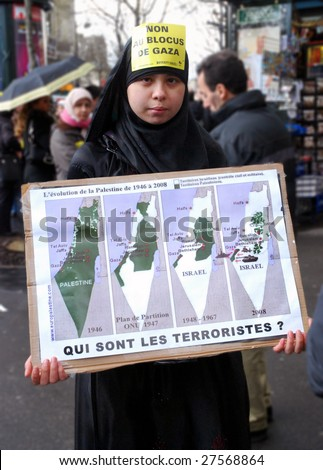 PARIS - MARCH 28: Anti-Israeli protester holds a poster during the manifestation on March 28, 2009 at Place du Chatelet in Paris, France. The poster says 'Who are the terrorists?' - stock photo