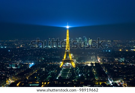 PARIS - MARCH 23: Cityscape of Paris with Eiffel Tower at night on March 23, 2012. The Eiffel tower is the most visited monument of France with about 6 million visitors every year. - stock photo