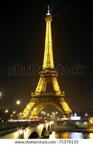 PARIS - MARCH 24: Lighting the Eiffel Tower March 24, 2011 in Paris. Established in 1985, the new system allowed the tower to glow golden glow. In February 2003, found 20,000 light bulbs. - stock photo