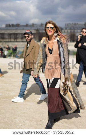PARIS - MARCH 8, 2016: Stylish European woman in the Tuileries Garden. Paris Fashion Week: Ready to Wear 2016/2017 is held from March 1 to 9, 2016.