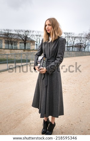 PARIS - MARCH 1, 2014: Stylish European woman with grey robe in the Tuileries Garden. Paris Fashion Week: Ready to Wear 2014/2015 is held from February 25 to March 5, 2014. - stock photo