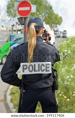 PARIS - MAY 20, 2014 - A french police woman control car speed with a mobile radar - stock photo