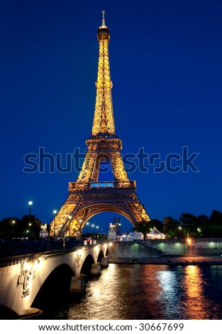 PARIS - MAY 17 : Illuminated Eiffel tower at dusk overlooking the River Seine May 17, 2009 in Paris. The Eiffel tower is one of the most recognizable landmarks in the world.