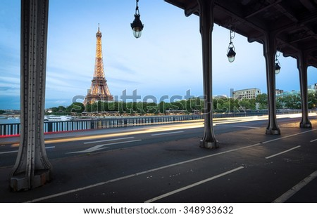 PARIS - MAY 5TH,2015: The illuminated Eiffel Tower and bridge Pont de Bir-Hakeim in on MAY 5TH,2015 in Paris, France.The Eiffel tower is most visited monument of France. - stock photo