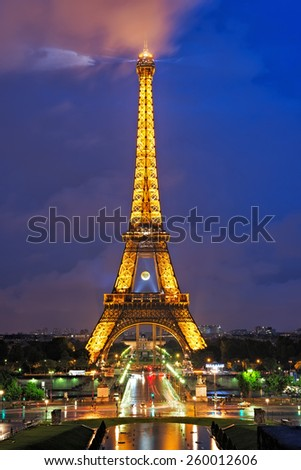 PARIS - MAY 28, 2014: The Eiffel tower is the most visited and recognized landmark in Paris. The illuminated tower at night is an added attraction. - stock photo