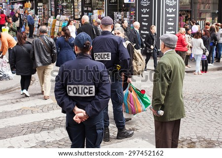 PARIS - May 15:Two uniformed Paris Police officers patrolling near the Sacre Coeur on May 15, 2013 in Paris, France - stock photo