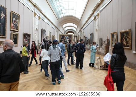 PARIS - MAY 3: Visitors at the Louvre Museum, May 3, 2013 in Paris, France. Louvre is the biggest Museum in Paris displayed over 60,000 sq.M. of exhibition space and very popular culture site - stock photo