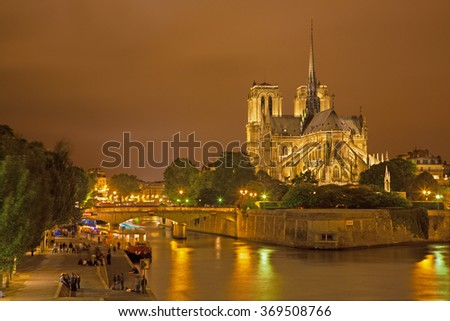 Paris - Notre-Dame cathedral in night and lot of young people on the riverside.   - stock photo