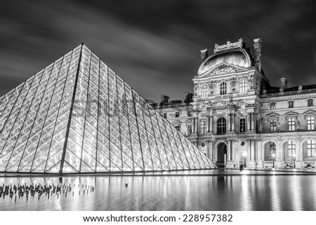 PARIS - NOV 1: Louvre Museum at twilight in autumn in black and white colors in November 1,2014. Louvre Museum is one of the world's largest museums with more than 8 million visitors each year. - stock photo