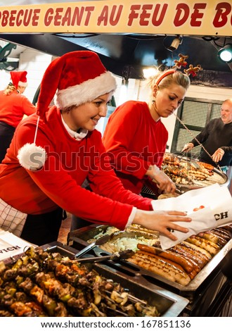 PARIS - NOV 30: Unidentified women in Santa Claus hats cook and sell hotdogs and barbecue at Christmas market  on November 30, 2013 in Paris, France. - stock photo
