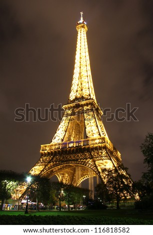 PARIS - OCTOBER 12: Eiffel Tower  at night seen from Champ des Mars  on October 12, 2012  in Paris, France . The tower was  erected in 1889 as the entrance arch to the 1889 World's Fair.
