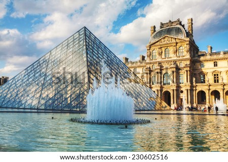 PARIS - OCTOBER 9: The Louvre Pyramid on October 9, 2014 in Paris, France. It serves as the main entrance to the Louvre Museum. Completed in 1989 it has become a landmark of Paris. - stock photo