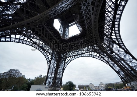 PARIS - OCTOBER 3: Tourists walk beneath Eiffel Tower in the evening of October 3, 2011 in Paris. Eiffel Tower is the most popular attraction of Paris, the most visited city in the world. - stock photo