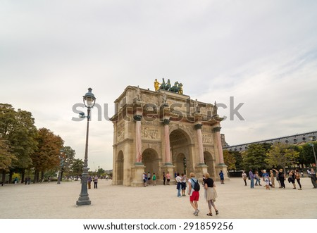 PARIS - SEPT 17, 2014: Tourists near the Arc de Triomphe du Carrousel. It is a triumphal arch in Paris, located in the Place du Carrousel and is derivative of the triumphal arches of the Roman Empire.