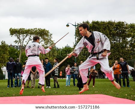 PARIS - SEPT 22: Two unidentified man perform Taekwondo jumping with sticks on September 22, 2013 in Paris, France. Famillathlon, action for raising awareness to sport, takes place in Champ de Mars. - stock photo