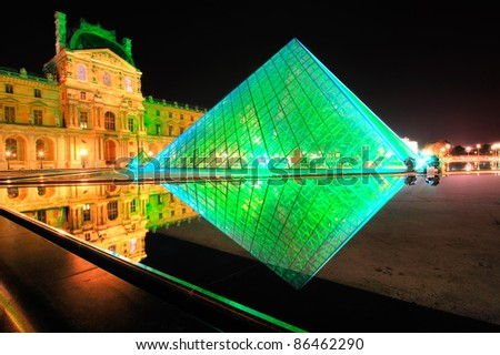 PARIS - SEPTEMBER 25: Louvre Pyramid shines at night during the autumn  September 25, 2011 in Paris. Louvre is the biggest Museum in Paris displaying over 60,000 square meters of exhibition space. - stock photo