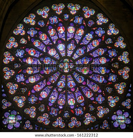 PARIS - SEPTEMBER 25: Rose stained glass window of Notre Dame Cathedral on september 25, 2013 in Paris. Notre Dame Cathedral was built in the 3rd century and is one of the main attractions of Paris. - stock photo