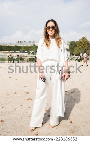 PARIS - SEPTEMBER 30, 2014: Stylish european woman with white dress in the Tuileries Garden. Paris Fashion Week: Ready to Wear 2014/2015 is held from September 23 to October 1, 2014. - stock photo