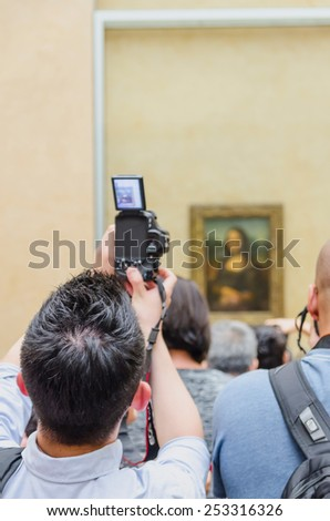 """PARIS - SEPTEMBER, 17: Visitors take photo of Leonardo DaVinci's """"Mona Lisa"""" at the Louvre Museum on September, 2014 in Paris, France. Gioconda is one of the world's most famous pictures.  - stock photo"""